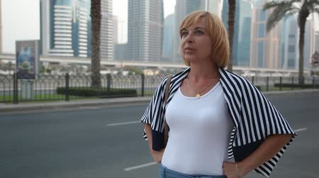 plášť : An exciting view of an elegant woman in a white T-shirt, jeans and a striped cloak waiting for somebody at highway in Dubai on a sunny day