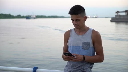 surfing the net : Portrait of a young man with a crew hairstyle in a singlet standing and touching the screen of his smartphone on a embankment with handrails at sunset