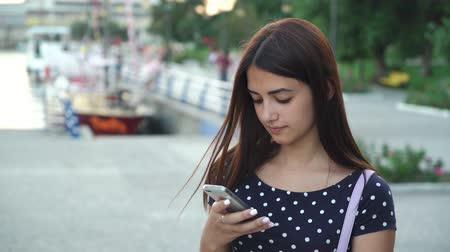 surfing the net : Portrait of a tender young woman in a polka-dot dress texting on her smartphone on river quay in a port with yachts at sunset in summer