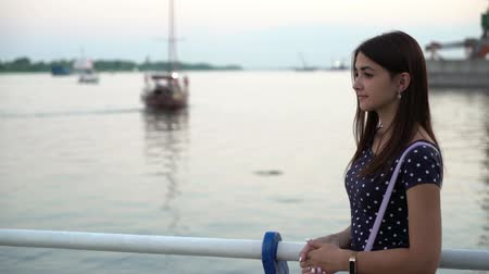 handrails : Profile of a beautiful young woman in a polka-dot dress standing on a river quay wiith shining waters and floating yacht at sunset in summer