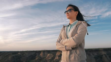 Profile of a stylish girl with long hair in black sunglasses in a sportive suit looking at horizonless sea surface and bending her elbows in summer