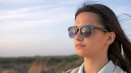 Profile of a top grade girl with long hair in black sunglasses in a sportive suit looking at sea surface on a coast under celeste sky in summer