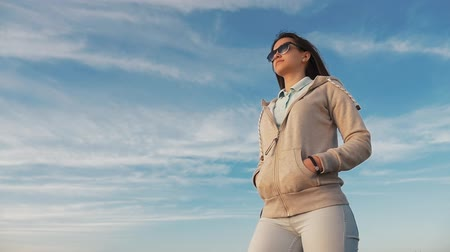 Profile of a stylish young woman in a sportive suit dreaming and standing on a seashore at a wonderful sunset with shining sun beams in summer Stok Video