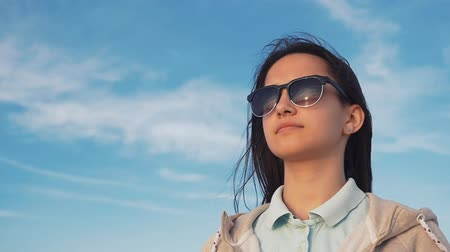 Profile of a gorgeous girl with long hair in black sunglasses in a sportive sweatshirt looking faraway on a sea coast under blue sky in summer