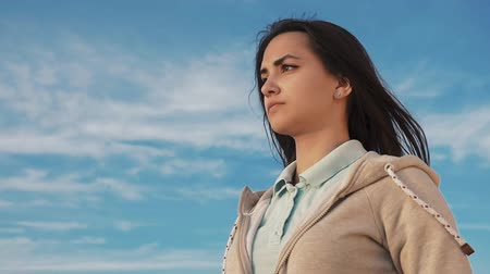 Down up view of a beautiful and confident young woman with long hair in a sportive hoodie looking beyond the horizon on a sea shore in summer Stok Video