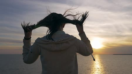 Back view of a stylish woman putting her fluttering hair in order while standing on the Black Sea coast at sunset with a golden sun path.