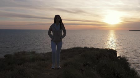 Back view of a dreaming young woman in a pastel sport suit standing on a green sea shore and enjoying the golden sunset with a sun path in summer Stok Video