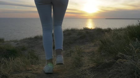 Back view of young female legs walking on a green grassy coast of the Black Sea with a splendid sunset and a shining sun path in summer