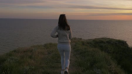 Back view of a slender young woman with long hair looking at a golden sunset with a sparkling sun path on the Black Sea shore in summer Stok Video