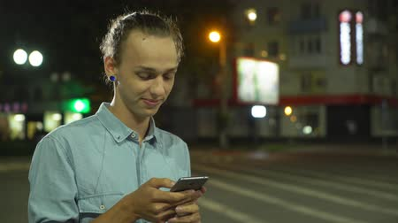 Profile of a cheery young man with a bun haircut surfing the net on his smartphone, smiling and seeking his sweetheart rin a street at night in autumn