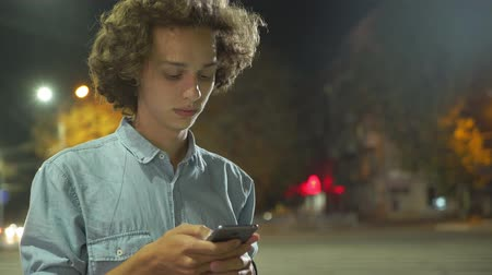 Profile of a handsome young man with long hair surfing the net on his smartphone and seeking photos of his girl  in a street deep at night in autumn Stok Video