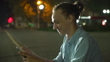 Profile of a laughing young man with a bun haircut browsing the net happily on his smartphone and seeking info in a city street deep at night in autumn