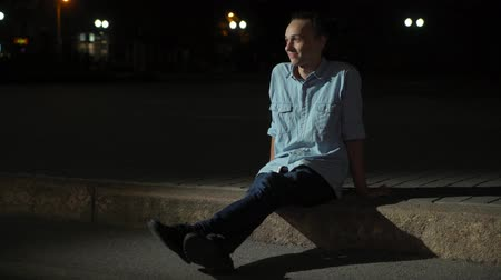 sleeve : Cheerful view of a young blond man with a bun haircut in a shirt and pants sitting on a city curb and smiling happily at night in autumn