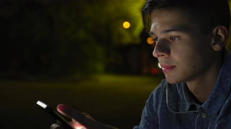 Astonishing view of a stylish brunet man with crew haircut looking at smartphone screen and browsing the net in a city at night in autumn. Stok Video
