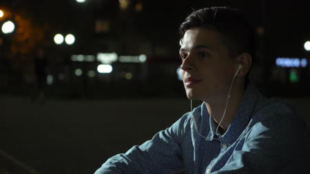Emotional view of a pensive young man with short haircut sitting on a pavement curb and listening to music through his earbuds in autumn