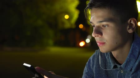 Exciting view of a romantic sportive man with short haircut looking at smartphone screen and seeking the photos of his darling at night.