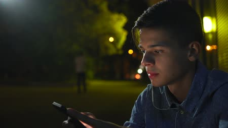 Impressive view of a romantic brunet man with short haircut looking at smartphone screen and seeking the photos of his sweetheart at night. Stok Video