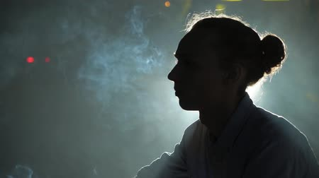 Profile of a Bohemian looking young blond man with a bun haircut sitting against a lamp and smoking a cigarette breathing out clouds of smoke in a street 影像素材