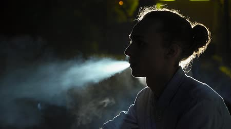 Profile of a young blond man with a bun haircut lighting a cigarette and blowing out a stream of smoke in a street at night in the autumn