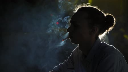 Profile of an arty looking young blond man with a bun hairstyle sitting and smoking a cigarette with clouds and streams of fume in a black studio Stok Video