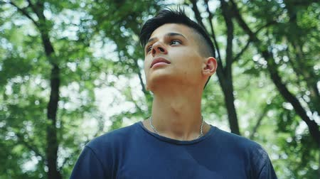 Down up view of a romantic young man with a short aircut  standing and looking thoughtfully in a leafy green wood on a sunny day