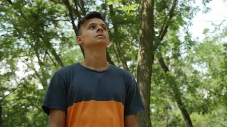 Down up view of a young brunet man with a crew haircut  standing and looking confidently in a green wood on a sunny day Stok Video