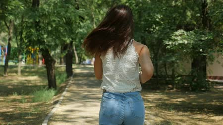 Back view of a slim young woman with long hair in jeans and a sleeveless blouse walking in a leafy forest with old trees and sunny lawns in summer