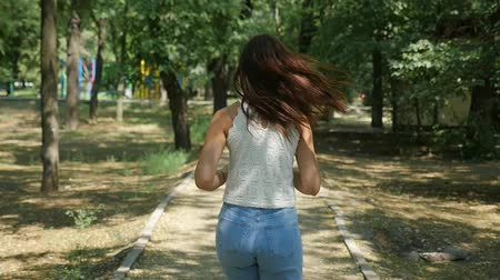 Back view of a slender young woman in jeans and a sleeveless blouse running slowly in a leafy forest with old trees and sunny lawns in summer