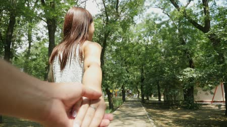 Cheerful view of a young woman in love with long loose hair and slim figure. She smiles and draws the hand of her friend in leafy park in summer. Stok Video
