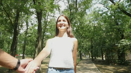 Wonderful view of an amorous young woman with long loose hair and slim figure. She smiles and pulls the hand of her friend in green park in summer.