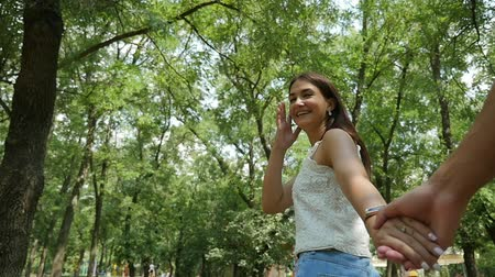 Cheerful view of an enamored young woman with long loose hair and slender figure. She smiles and pulls the hand of her Mr.Right in green park in summer.