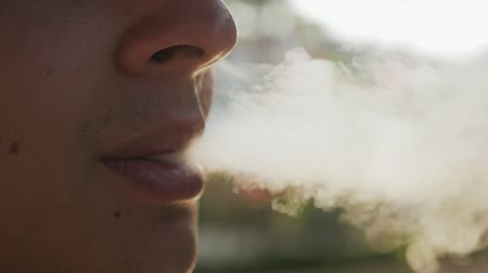 yanaklar : Macro shot of a young man taking a toke and breathing out thick smoke from his electronic cigarette outdoor on a sunny day in summer in slow motion