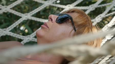 frondoso : Closeup of a sleeping blond woman in black sunglasses having a rest in a hammock from networking ropes on a sunny day in summer in slow motion