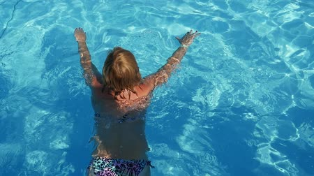 delgado : Up down view of a cheery blond woman in bikini swimming breaststroke in a swimming pond with sparkling light blue waters in summer in slow motion Stock Footage