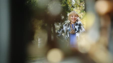 delgado : Bokeh portrait of an elegant blond woman in a plaid woolen jacket seen through metallic fencing chatting on her smartphone in a green park in autumn.