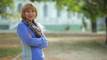 впечатляющий : Exciting view of a fashionable blond woman with a bob haircut in a sweatshirt and a scarf  standing with crossed arms in semi-profile in autumn Стоковые видеозаписи