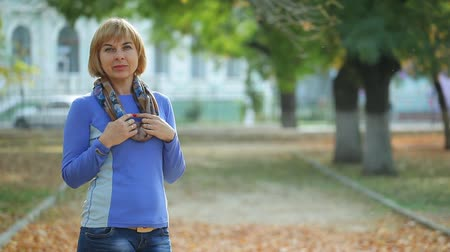 delgado : Cheerful view of an elegant blond woman with a bob haircut in sportive  sweatshirt, jeans and a silk scarf  standing and smiling in a park in autumn