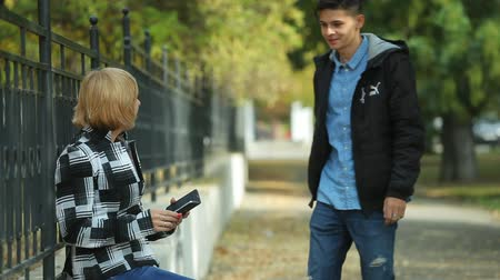 surfing the net : Impressive profile of a blond woman in plaid jacket with a phone and her young man approaching her and taking a seat on parapet in a park