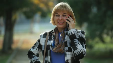 otimismo : Bokeh portrait of a happy blond woman in a plaid woolen jacket and a scarf talking on her smartphone and smiling romantically in a park in autumn.