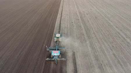 arado : Back bird`s eye view of a powerful agricultural tractor drawing wide plows with dozens of mouldboards and cultivating an agro field in autumn