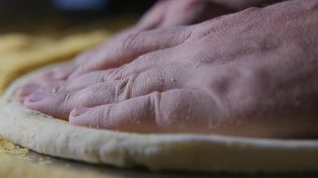 klasa : Impressive macro shot of chef hands spreading and pressing fresh dough for pizza on a metallic table with yellow grains and in a kitchen in slow motion