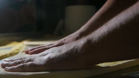 капуста : Arty closeup of male hands spreading, spinning, replacing and making fresh dough to cook a pizza on a metallic table in a kitchen in slow motion