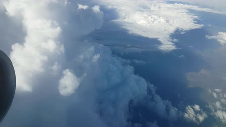 montanhoso : Stunning view of huge and fluffy white clouds from an airplane window on sunny day in summer. Sky clouds look like raggy mountains. Vídeos