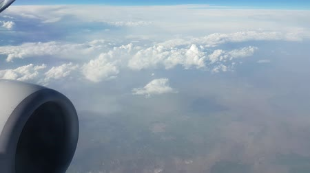 rongyos : Enigmatic view of humpy and bumpy white clouds from an airplane window on sunny day in summer.The sparkling celeste sky is above Stock mozgókép