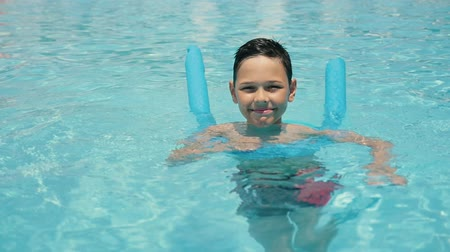 lengthy : Cheery view of an entertaining small brunet boy with lenghty plastic tubes bathing in a swimming pool with transparent blue waters in slo-mo