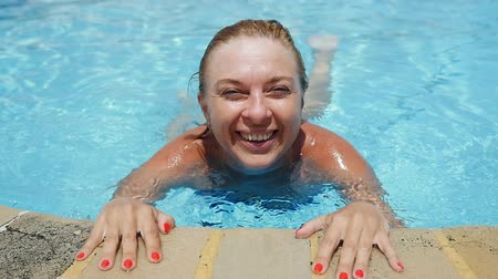 cheerfulness : Cheerful view of happy stylish blond woman bathing and holding the wading pond edge while enjoying life in swimming pool with see-through water in slo-mo Stock Footage