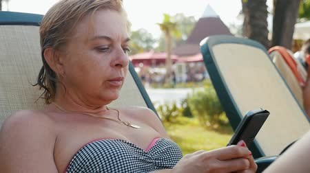 sending : Splendid view of an elegant blond woman in striped bikini sitting in a recliner outdoors and surfing net on smartphone looking at various photos in slo-mo