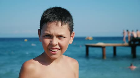 dojem : Portrait of a happy small boy with a big smile and screwed up eyes standing on sea beach with a lond platform behind him in summer in slow motion