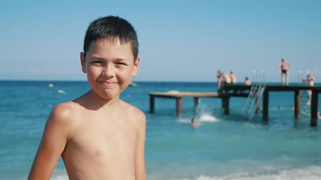 izlenim : Midshot of a funny small boy with a big smile and screwed up eyes standing on sea beach with a wooden platform behind him in summer in slow motion