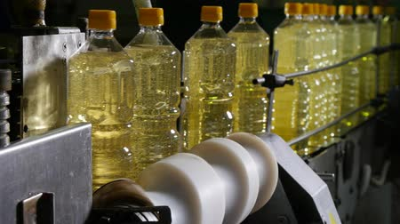 高度な : Stunning closeup of plastic bottles with sunflower oil advanciig in conveyor in the black backdrop. It looks optimistic and businesslike.